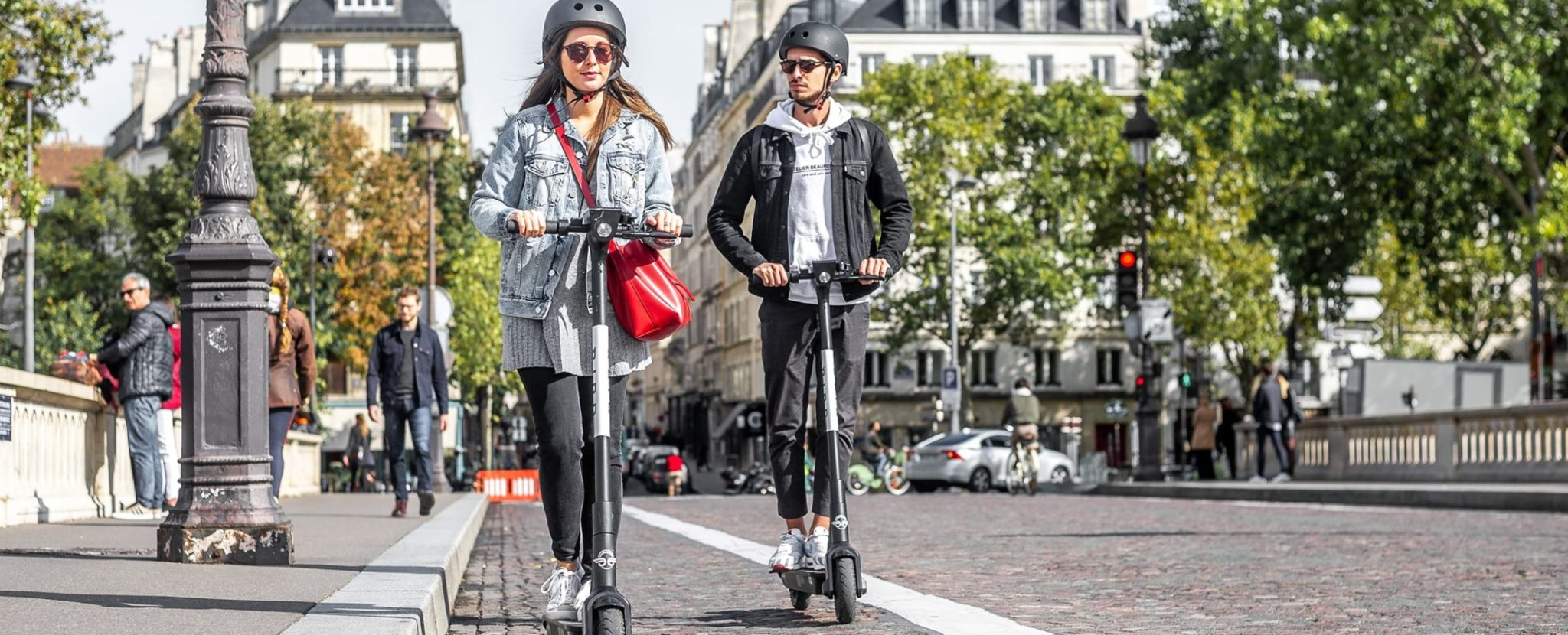 Girl and boy on e-scooter in city
