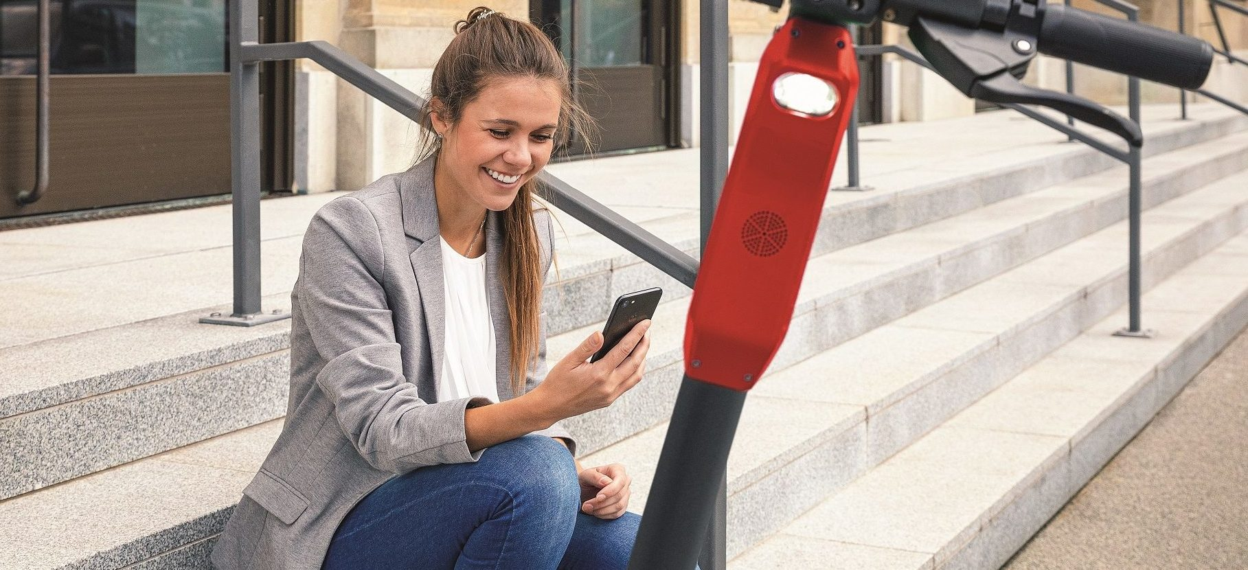 Girl sitting on stairs in front of e-scooter